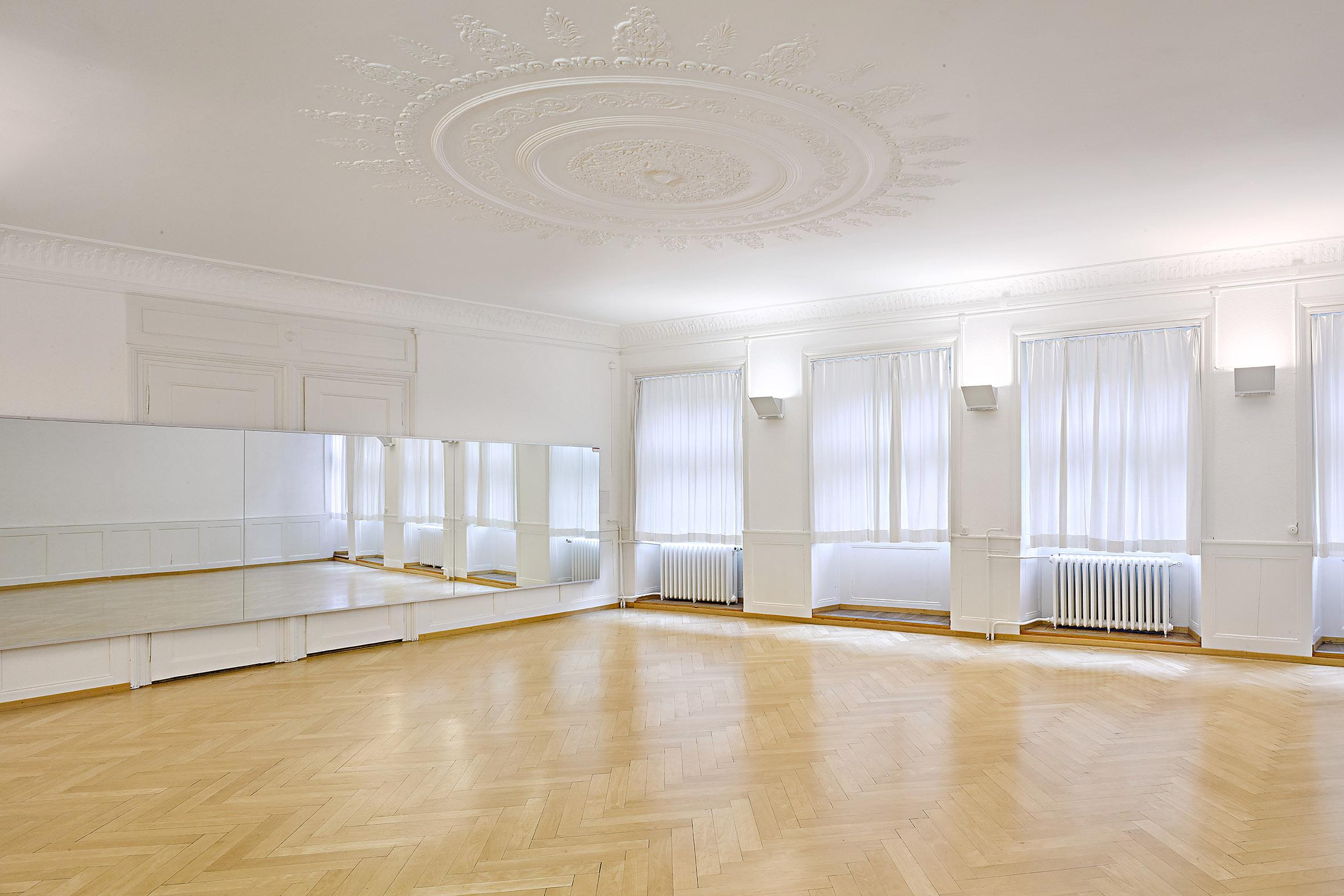 Ein grosser Saal mit weissen Wänden und Holzboden. An der Wand befindet sich ein grosser Spiegel und an der Decke schöner Stuck. Ausserdem tritt viel Tageslicht durch die grossen Fenster.