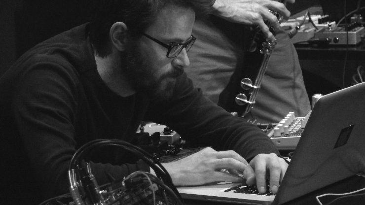 Ein Mann mit Brille sitzt vor einem Laptop, dahinter erkennt man einen anderen Mann an einer Klarinette.