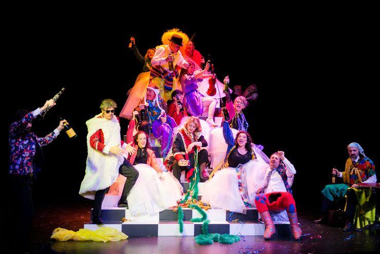 Une pyramide humaine de femmes et d'hommes qui portent des vêtements colorés et tiennent des bouteilles et des instruments de musique dans leurs mains.