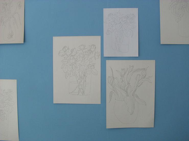 Dessins de bouquets de fleurs sur papier blanc, sur un mur bleu.