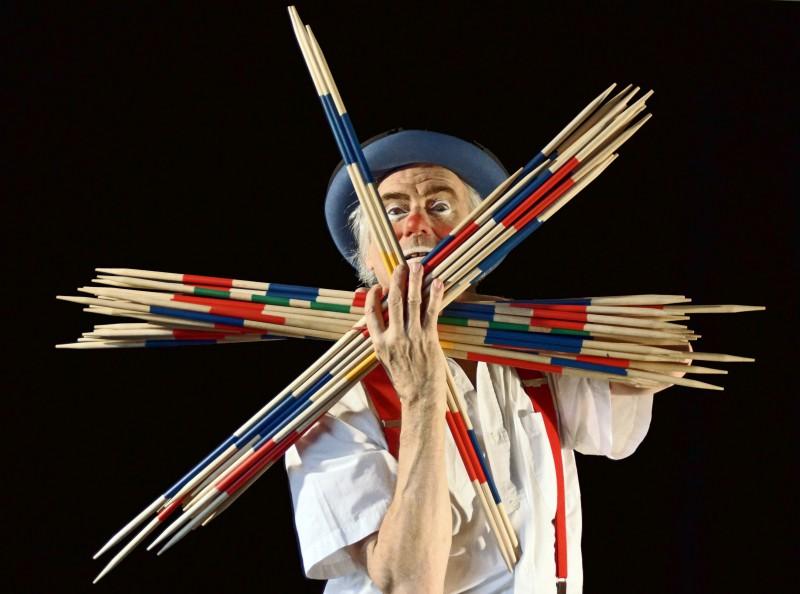 Un clown tient de gros bâtons de Mikado devant son visage.