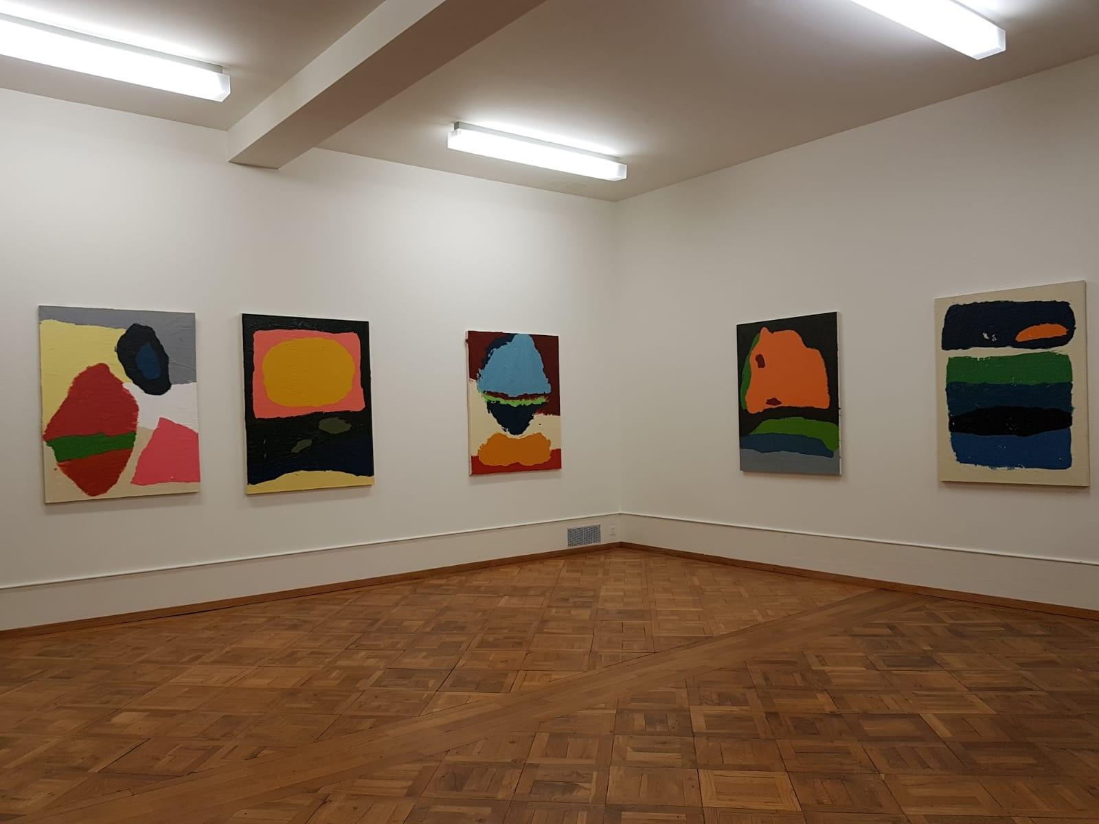 In einem Saal mit Holzboden und weissen Wänden hängen 5 gemalte, abstrakte und bunte Bilder.