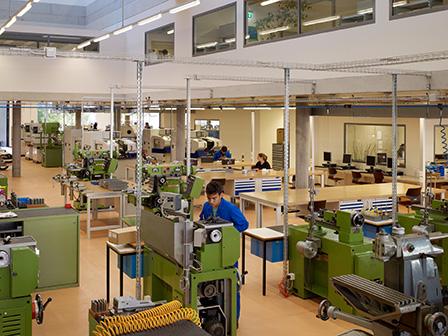 Vue intérieure du lycée technique de Bienne. La rénovation a eu lieu en 2016 et a obtenu la première place du «Prix Engagement Economique». La photo montre une grande salle avec différentes machines sur lesquelles travaillent des jeunes en formation.