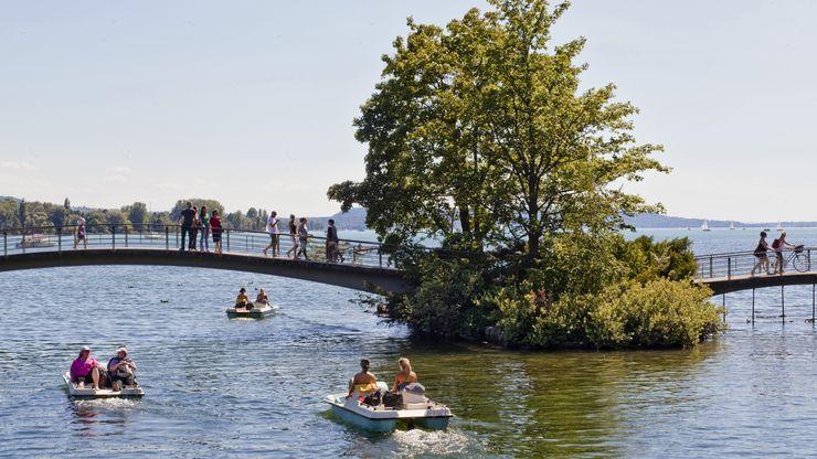 Pédalos sur le lac de Bienne passant sous le pont piétonnier des Prés-de-la-Rive
