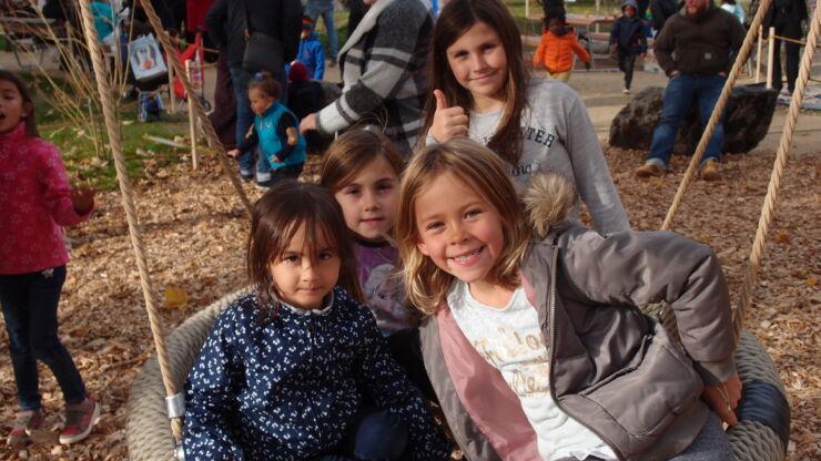 Einweihungsfest Kinderspielplatz Bergfeld: Eine Gruppe von Mädchen auf einem Schaukelring aus Schnur
