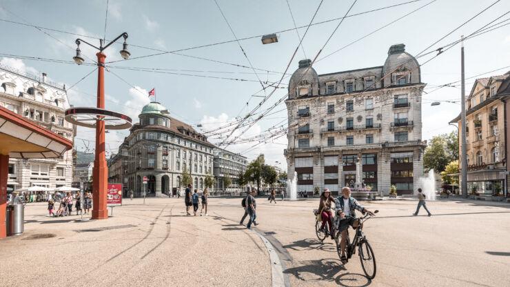 Vue sur la place Centrale en direction du Bâtiment du Contrôle avec des piétons et des cyclistes