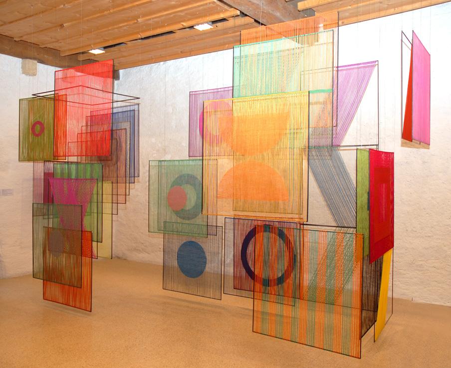 In einem Raum ist eine farbenfrohe Installation zu sehen. An freischwebenden und geometrischen Stangen, wurden bunte Fäden mit verschiedenen Mustern geflochten.