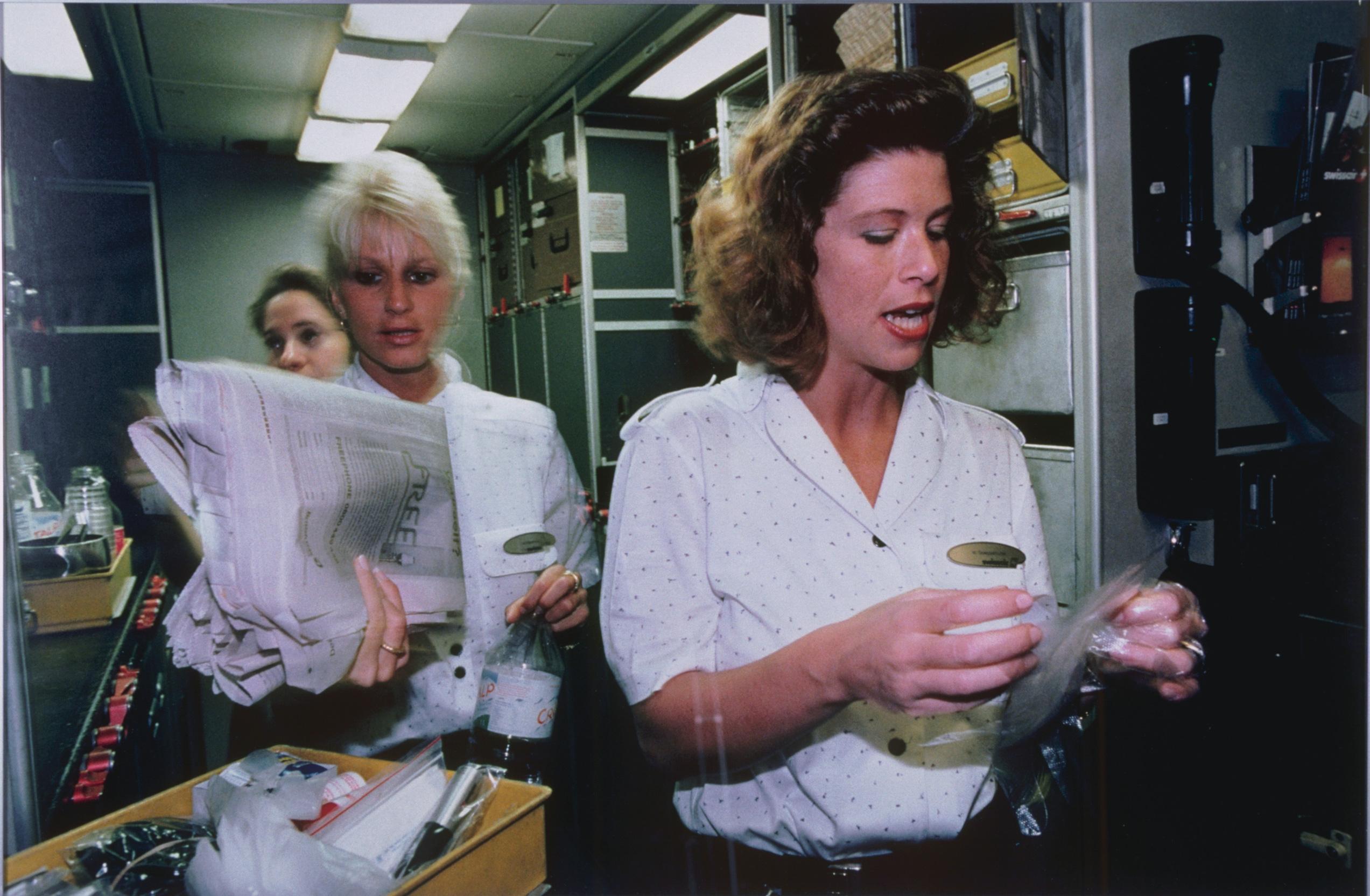 La photo montre trois femmes avec des chemisiers blancs. Une femme tient un journal et une bouteille d'eau et une autre tient quelque chose enveloppé dans du plastique. EIles portent également un badge doré.