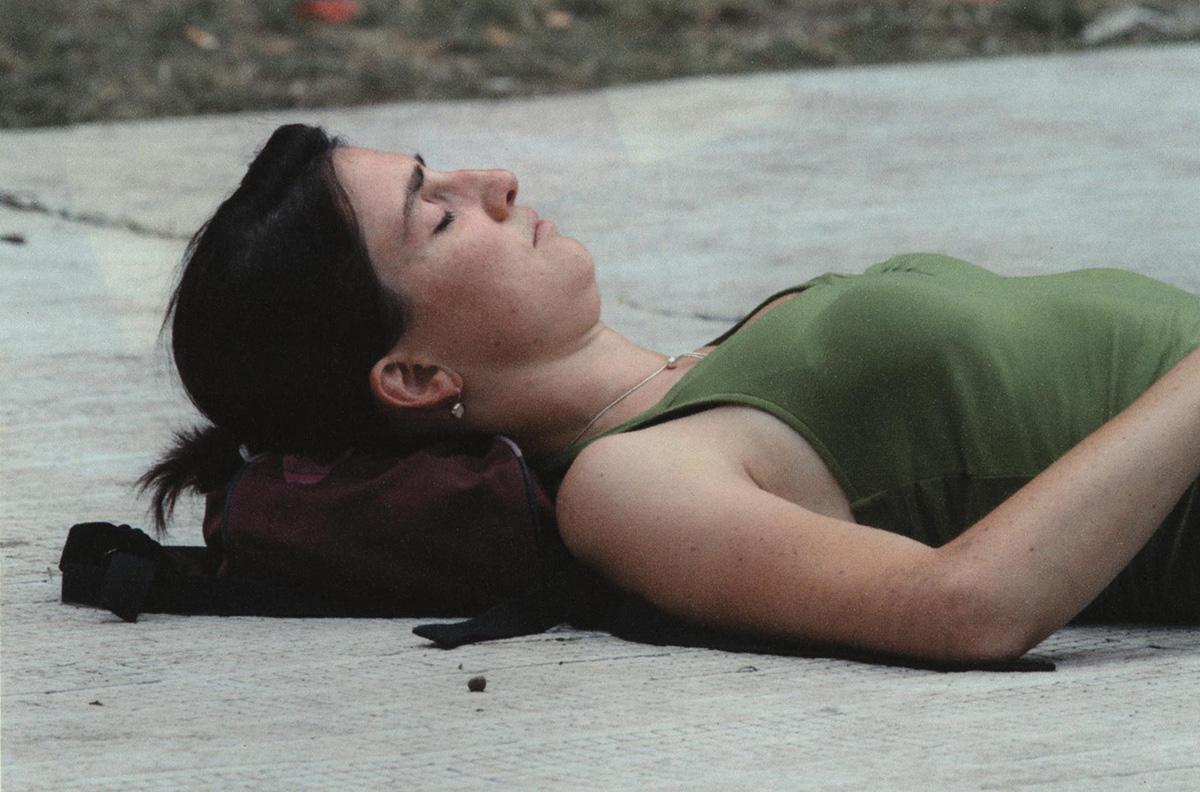 Man sieht der Oberkörper einer Frau mit dunklen Haaren und grünem Trägertop auf dem Boden liegend. Die Augen sind geschlossen und der Kopf liegt auf einem Rucksack auf.