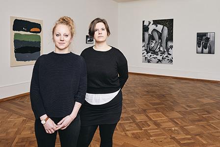 Zwei Frauen mit schwarzen Pullovern, die eine hat rotes Haar, die andere braunes stehen in einem Raum, wo im Hintergrund ein Bild und ein Holzboden zu erkennen ist.