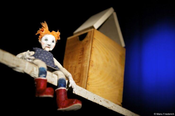 Une petite poupée aux cheveux oranges, robe bleue et bottes rouges repose sur une planche de bois. A côté se trouve une boîte en bois, sinon l'image est noire.
