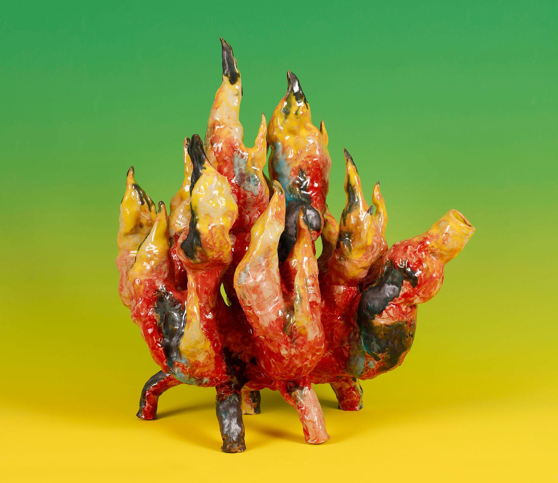 Sur un fond jaune-vert se dresse une sculpture de verre colorée qui rappelle fortement les flammes.