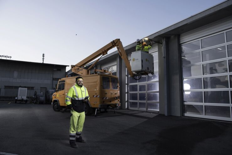 Un employé d'ESB Energie Service Biel/Bienne, en habit de service jaune fluorescent, se tient devant le hangar de nuit. En arrière-plan, deux autres employés sont dans un élévateur et réparent un lampadaire.
