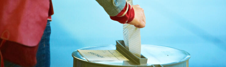 Une personne, dont on ne voit que la main, glisse un bulletin de vote dans une urne