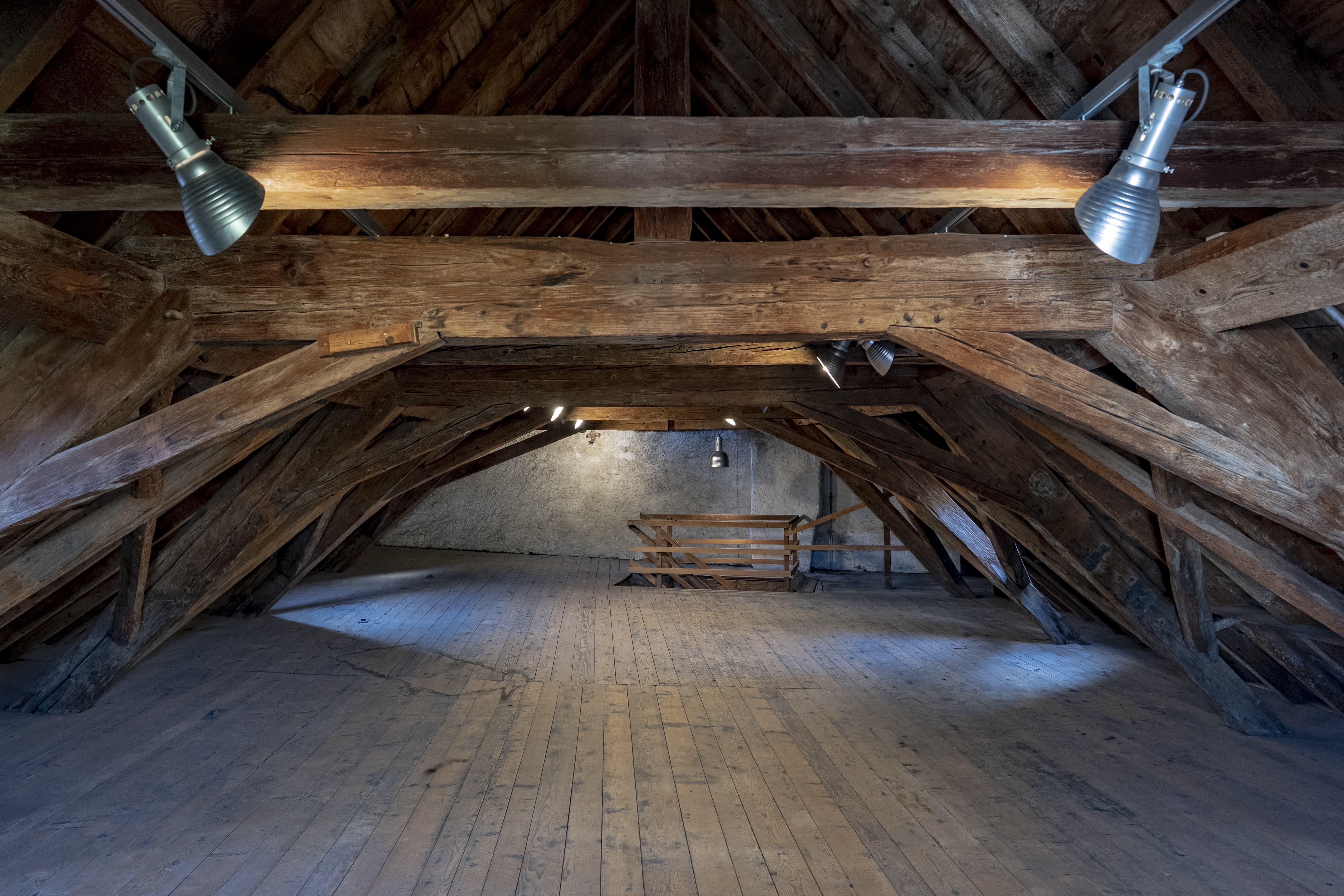 Ein Dachstock aus Holz mit Lampen an der Decke.
